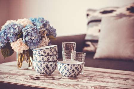 hortensia 꽃과 유리의 꽃다발 현대 나무 커피 테이블과 베개와 아늑한 소파에 그릇. 거실 인테리어 및 홈 장식 개념. 톤의 이미지