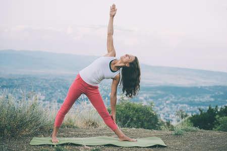 mujeres de espalda: Joven practicar yoga al aire libre en la naturaleza con la ciudad en el fondo. imagen de tonos