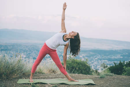back: Young woman practicing yoga outdoor in the nature with city on background. Toned image