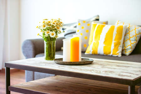 YELLOW: Modern wooden coffee table and cozy sofa with pillows. Living room interior and home decor concept Stock Photo