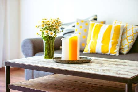Moderner Couchtisch aus Holz und gemütlichen Sofa mit Kissen. Wohnzimmerinnenraum und Wohngestaltung-Konzept