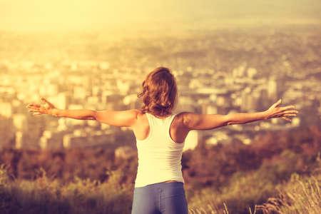Mladá žena šíření ruce dokořán s městem na pozadí. Pojetí svobody. Láska a emoce, žena štěstí. Tónovaný obraz