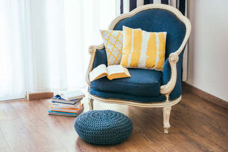 home furniture: Cozy armchair with open book and decorative pillows. Interior and home decor concept