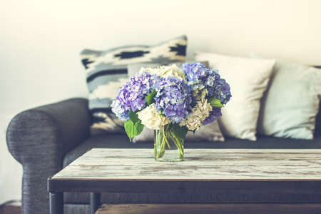 Bouquet of hortensia flowers on modern wooden coffee table and cozy sofa with pillows. Living room interior and home decor concept. Toned image
