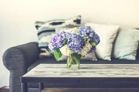 Bouquet von Hortensien Blumen auf moderner Couchtisch aus Holz und gemütlichen Sofa mit Kissen. Wohnzimmerinnenraum und Wohnkultur Konzept. Getönt
