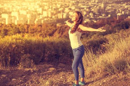 Junge Frau, die Verbreitung Hände breit mit Stadt im Hintergrund öffnen. Freiheit Konzept. Liebe und Emotionen, Frau, Glück. Getönt