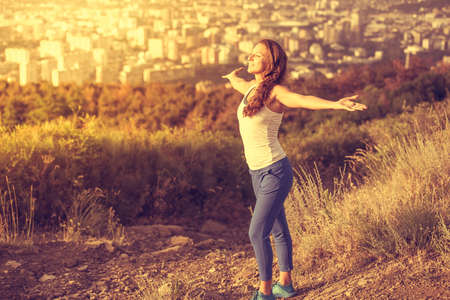 Young woman spreading hands wide open with city on background. Freedom concept. Love and emotions, woman happiness. Toned image Zdjęcie Seryjne - 50414024