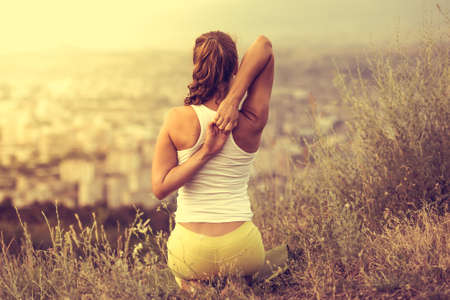Young woman sits in yoga pose with city on background. Freedom concept. Calmness and relax, woman happiness. Toned image Standard-Bild