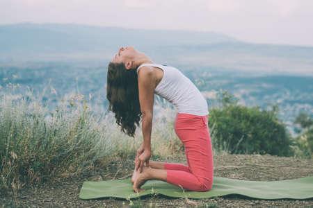 Giovane donna praticare yoga all'aperto nella natura con la città sullo sfondo. Viraggio