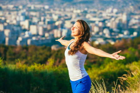 Young woman spreading hands wide open with city on background. Freedom concept. Love and emotions, woman happiness. Stockfoto