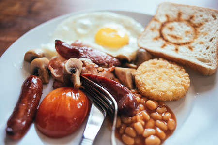 Traditional English breakfast with bacon, sausage, mushrooms, tomatoes, fried egg, hash browns and baked beans. Served with toast Banco de Imagens