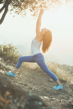 Young woman practicing yoga outdoor in the nature with city on background. Toned image photo