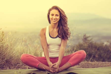 Mujer joven se sienta en pose de yoga con la ciudad en el fondo. Concepto de la libertad. La calma y relajarse, mujer felicidad. Imagen entonada Foto de archivo