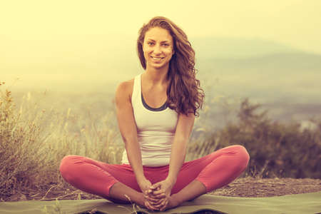 Young woman sits in yoga pose with city on background. Freedom concept. Calmness and relax, woman happiness. Toned image photo