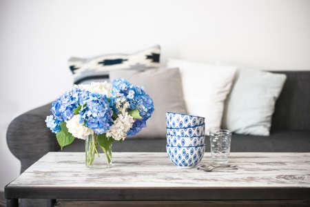 Boeket hortensia bloemen en glas kommen op moderne houten salontafel en gezellige bank met kussens. Woonkamer interieur en home decor Het concept