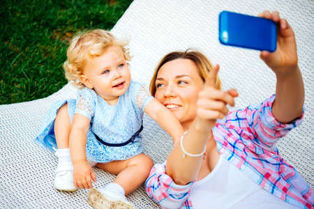 parents with baby: Mother points to her smartphone to take a selfie with her daughter Stock Photo