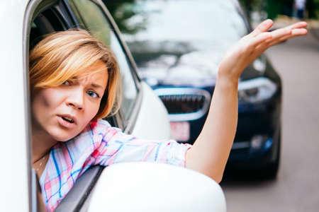 젊은 여자가 교통 체증에 차를 운전하는 동안 짜증이옵니다.