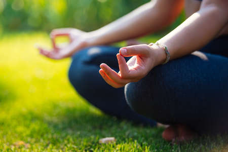 Yoga meditation in park, healthy female in peace, soul and mind zen balance concept. Selective focus and shallow DOF