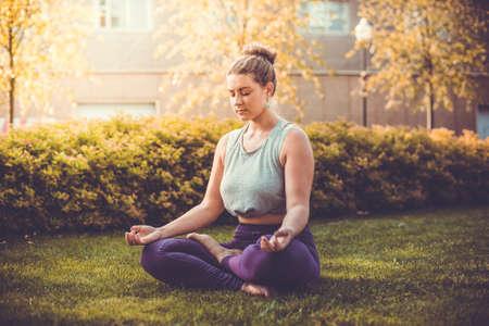 donne obese: Meditazione Yoga in posizione del loto nel parco. Giovane donna in pace, anima e spirito zen concetto. tonica immagine