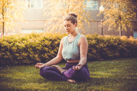 overweight girl: Yoga meditation in lotus pose in park.  Young woman in peace, soul and mind zen balance concept. Toned picture Stock Photo