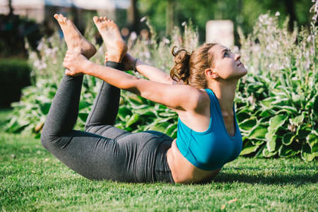 bends: Young woman practicing yoga and doing backward bending pose in park