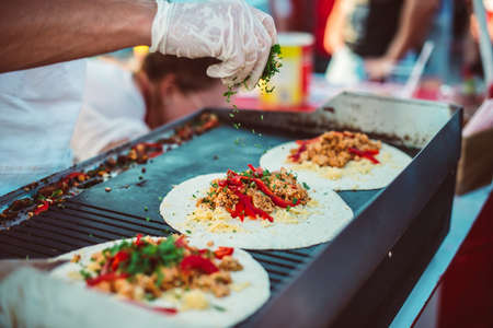 Preparation of fajitas, mexican beef with grilled vegetable in tortilla wraps. Street food and outdoor cooking concept Stockfoto