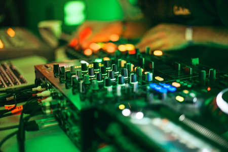 electronic music: DJ is performing during the night. Closeup of djs controller with selective focus. Stock Photo