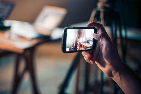 사람이 스마트 폰으로 사진을 복용한다.