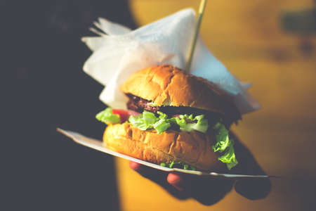 Closeup of home made burger in hand. Toned picture Stock Photo