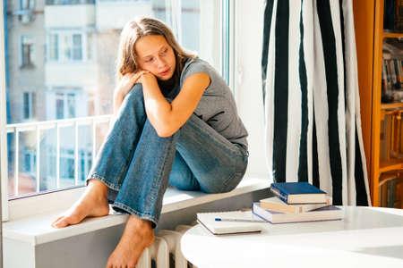 niña pensando: Una adolescente triste se sienta en el alféizar de la ventana en lugar de la lectura de libros sobre la mesa
