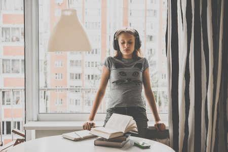 Smutna nastolatka siedzi na parapecie słuchając muzyki, zamiast czytać książki na stole. Stonowanych obraz Zdjęcie Seryjne
