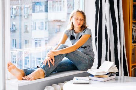 teenager thinking: Una adolescente triste se sienta en el alf�izar de la ventana mirando libros sobre la mesa