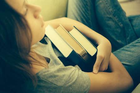 슬픈 10 대 소녀가 책을 들고 안락의 자에 앉는 다. 톤 이미지