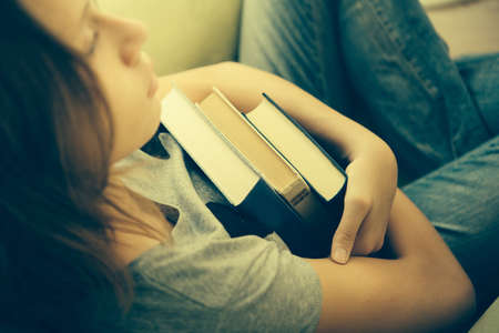 A sad teenage girl sits in armchair holding books. Toned image