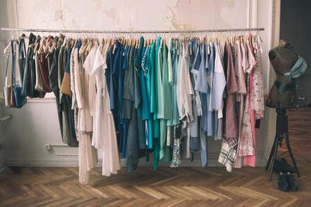 Färgstarka kvinnornas klänningar på hängare i en butik. Mode shoppingkoncept. tonad bild