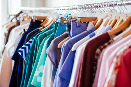 casual clothes: vestidos de las mujeres coloridas en perchas en una tienda al por menor. La moda y las compras concepto Foto de archivo