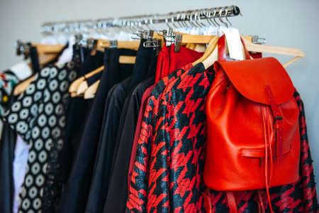 vestidos de las mujeres coloridas en perchas en una tienda al por menor. La moda y las compras concepto