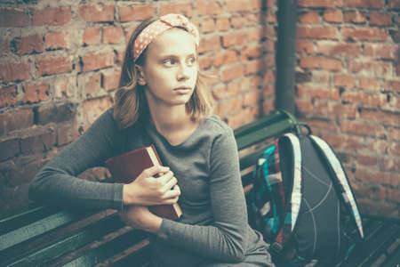 A portrait of a teenage girl sitting on a bench holding a book with brick wall in the background. Toned image