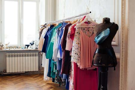 tienda de ropa: vestidos de las mujeres coloridas en perchas en una tienda al por menor. La moda y las compras concepto Foto de archivo