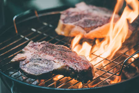 florentine: Two t-bone florentine beef steaks on the grill with flames. Toned picture Stock Photo