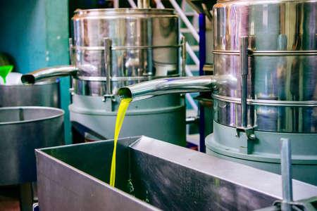 Petróleo está vertiendo desde el tubo en una fábrica en frío de prensa después de la cosecha de oliva en una de las aldeas de Sicilia, Italia Foto de archivo