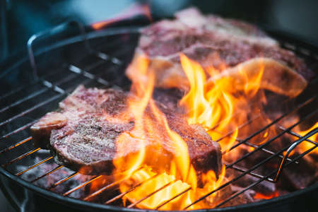 Two t-bone florentine beef steaks on the grill with flames Stock Photo
