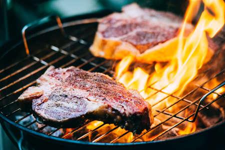 Due t-bone bistecche alla fiorentina di manzo alla griglia con le fiamme Archivio Fotografico