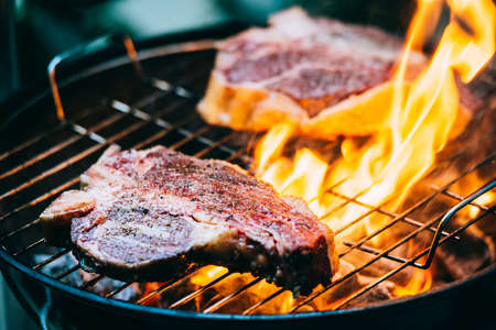 barbecue fire: Two t-bone florentine beef steaks on the grill with flames Stock Photo