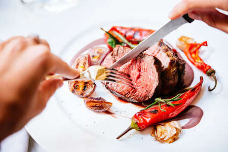Person cuts beef steak with grilled vegetables served on white plate Stock Photo