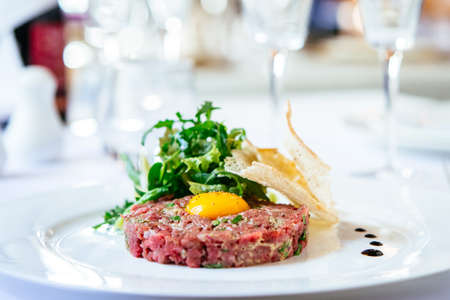 Beef tartare with arugula salad, egg yolk and crisp bread chips on white plate Stock Photo