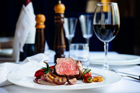 Filete de carne con verduras asadas servido en un plato blanco Foto de archivo - 50540394