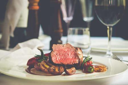 Beef steak with grilled vegetables served on white plate. Toned picture