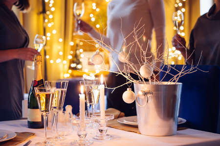 party people: Christmas or New Year party table with champagne. Three persons stand behind