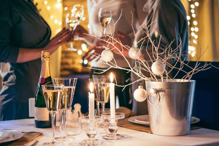 christmas light: Christmas or New Year party table with champagne. Three persons stand behind